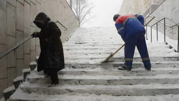 Сотрудник коммунальных служб убирает снег с лестницы подземного перехода во время снегопада в Москве. 4 февраля 2018
