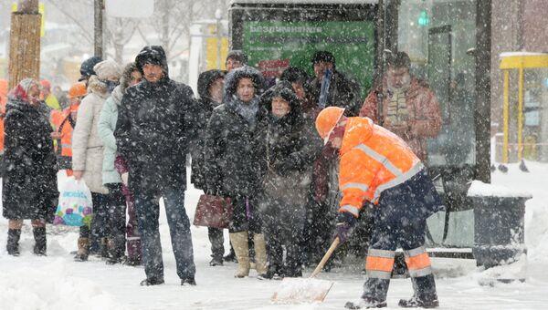 Жители на остановке общественного транспорта на Тверской улице во время снегопада в Москве. Архивное фото