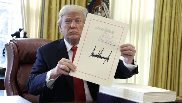 Президент США Дональд Трамп демонстрирует подписанный налоговый законопроект. 22 декабря 2017