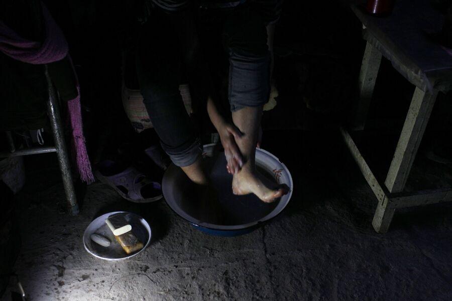Марина моет ноги в подвале, где живет с семьей. Спартак, Донецкая народная республика