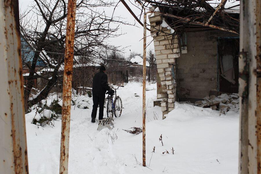Житель поселка Спартак идет между разрушенными домами. Спартак, Донецкая народная республика