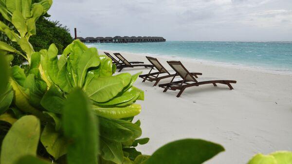 Шезлонги на пляже острова Велассару (Мальдивы)