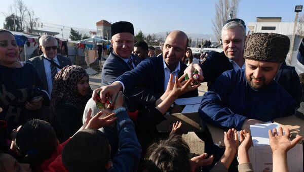 Участники межконфессиональной делегации религиозных деятелей из России во время раздачи гуманитарной помощи в палаточном лагере для сирийских беженцев в долине Бекаа в Ливане