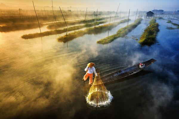 Снимок Рыбалка на восходе солнца (Sun's Up, Nets Out) фотографа Zay Yar Lin, занявший первое место в категории Пейзаж.Профессионалы