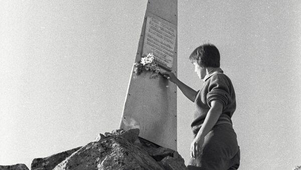 Женщина возлагает цветы к памятнику советским воинам на перевале Донгузорун