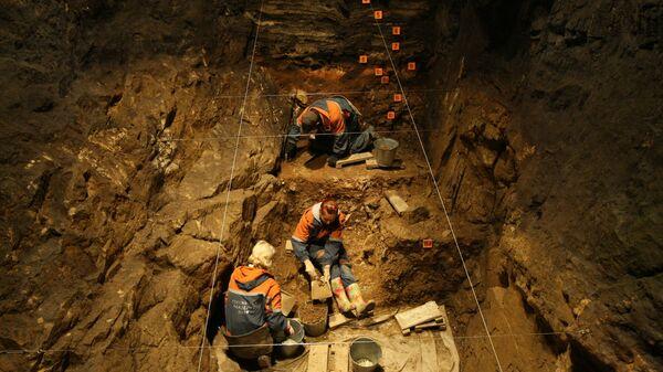Сотрудники Института археологии и этнографии Сибирского отделения РАН во время археологических работ в одной из галерей Денисовой пещеры