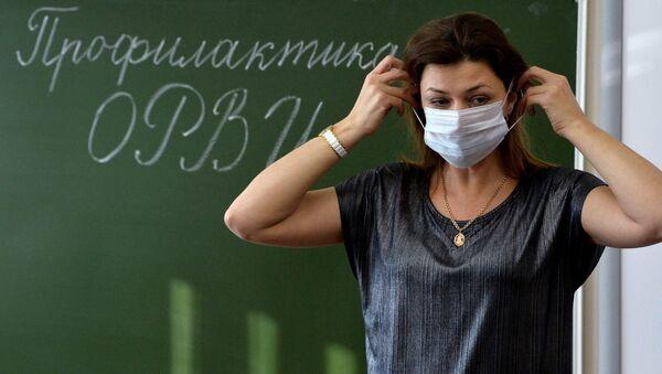 Учительница начальных классов гимназии № 96 в Челябинске объясняет ученикам правила использования медицинских масок в целях профилактики гриппа ОРВИ