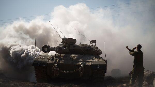Израильский солдат и танк на Голанских высотах в районе границы с Сирией. Архивное фото