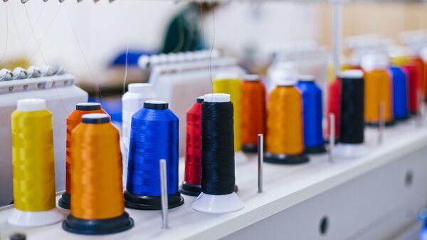 Катушки с нитками на вышивальном оборудовании в швейном цехе