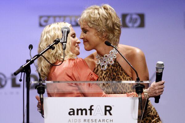 Американская актриса Шэрон Стоун приветствует Мадонну во время ежегодного благотворительного вечера AmfAR Кино против СПИДа в Мужен, Франция. 22 мая 2008 года