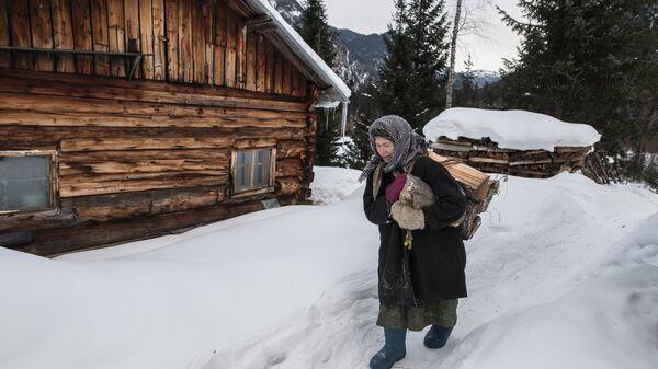 Отшельница из семьи староверов Агафья Лыкова идет с вязанкой дров по своей заимке