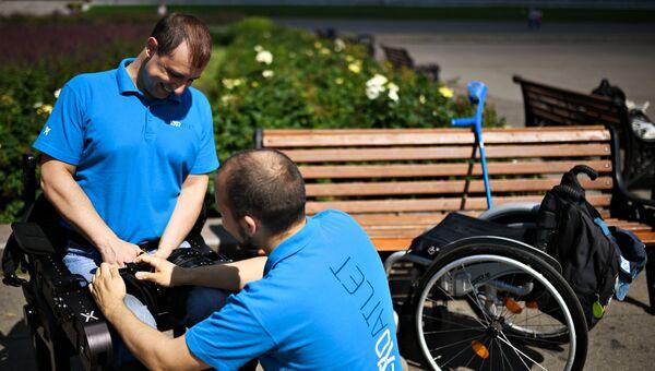 Сопровождающий помогает Виталию Данилову надеть экзоскелет.