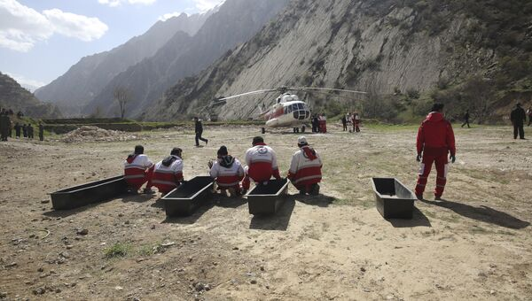 Члены спасательной команды ждут погрузки тел пассажиров турецкого частного самолета, который разбился в горах Загрос в Иране. 12 марта 2018
