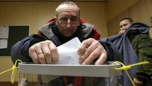 Мужчина во время досрочного голосования на выборах президента РФ в Мурманской области. 13 марта 2018