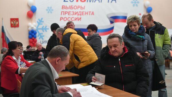 Избиратели во время голосования на выборах президента Российской Федерации на избирательном участке в Байконуре. 18 марта 2018