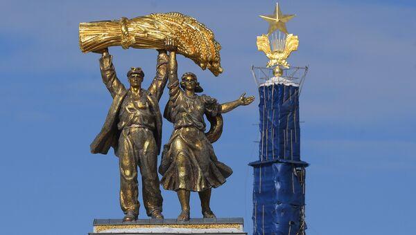 Скульптура Тракторист и колхозница на арке Главного входа ВДНХ. На втором плане - золотая звезда на шпиле Центрального павильона ВДНХ после реставрации.