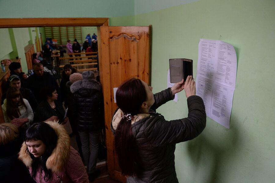 Женщина фотографирует на мобильный телефон списки пропавших без вести при пожаре в торговом центре Зимняя вишня в Кемерово