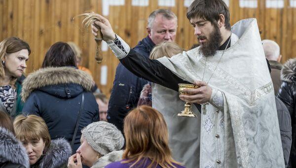 Священник проводит обряд с родственниками подстардаших при пожаре в ТЦ Зимняя вишня в Кемерово. 26 марта 2018