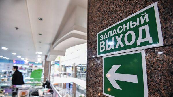 Указатель и знак Запасный выход в торговом центре