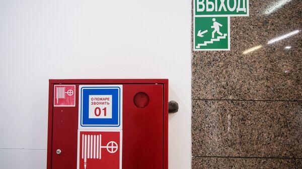 Пожарный шкаф и указатель направления эвакуации при пожаре в торговом центре. Архивное фото