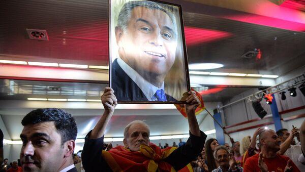 Мужчина с портретом лидера Демократической партии социалистов Черногории Мило Джукановича во время президентских выборов
