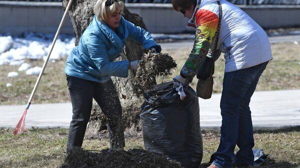Женщины убирают прошлогоднюю листву во время городского субботника в Москве