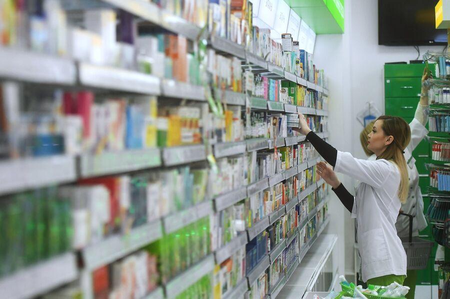 Фармацевт раскладывает лекарственные препараты в аптеке сети Ригла на Арбате в Москве