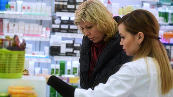 Фармацевт обслуживает посетителя в аптеке в Москве