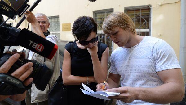 Молодой человек Дмитрий, купивший путевку у прекративший работу туристической компании Интаэр, показывает журналистам договор