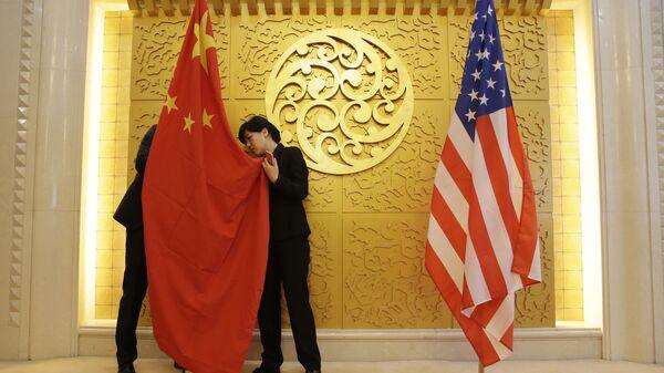 Служащие устанавливают флаг Китая перед встречей министра транспорта Китая Ли Сяопэна и министра транспорта США Элейн Лан Чао