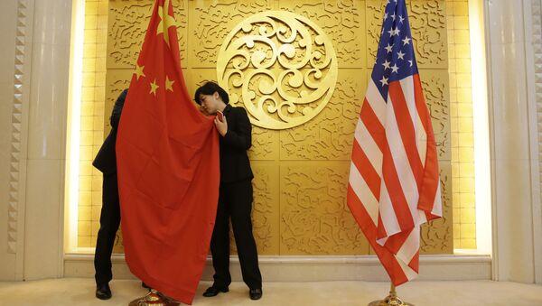 Служащие устанавливают флаг Китая перед встречей министра транспорта Китая Ли Сяопэна и министра транспорта США Элейн Лан Чао. Архивное фото