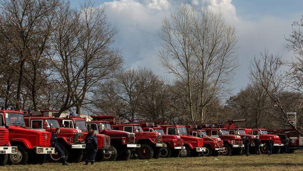 Пожарные расчеты автомашин рядом с военными складами боеприпасов в Харьковской области, где произошел пожар. Архивное фото