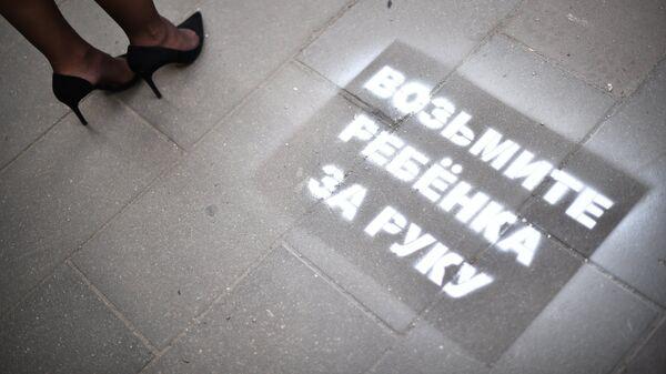 Предупреждающая надпись для пешеходов, нанесенная на дороге перед переходом
