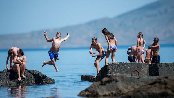 Отдыхающие прыгают в воду с волнорезов в Новом Свете