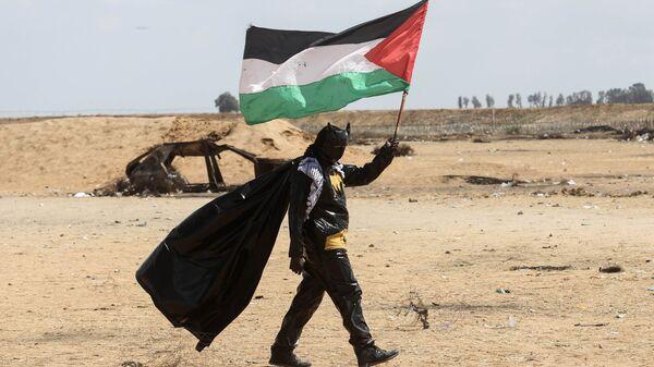 Палестинский протестующий, одетый в костюм Бэтмена, на границе между сектором Газа и Израилем