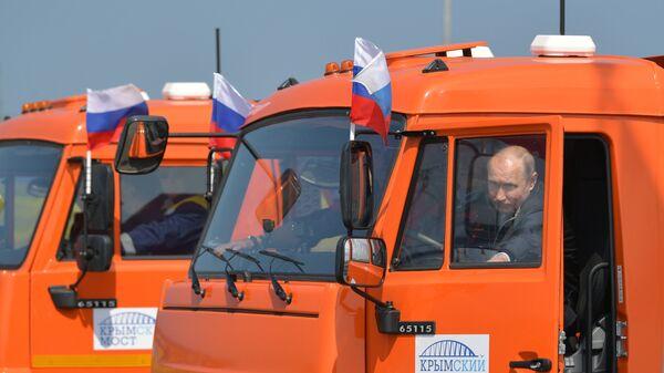 Президент РФ Владимир Путин садится за руль автомобиля КамАЗ во время проезда колонны строительной техники по автодорожной части Крымского моста. 15 мая 2018