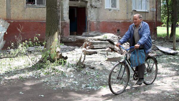 Мужчина едет на велосипеде во дворе жилого дома, пострадавшего в результате обстрела, в поселке Горловка Донецкой области. Архивное фото