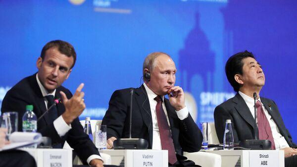 Президент РФ Владимир Путин, президент Франции Эммануэль Макрон и премьер-министр Японии Синдзо Абэ на Петербургском международном экономическом форуме. 25 мая 2018. Архивное фото