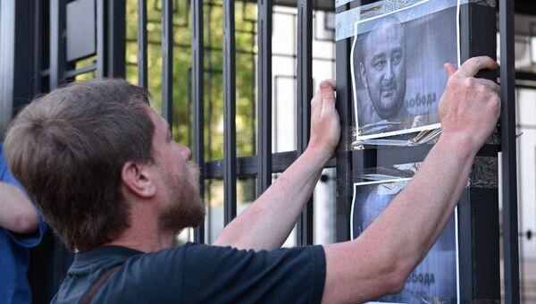 Мужчина клеит листовки с портретом убитого российского журналиста Аркадия Бабченко у здания посольства РФ в Киеве. 30 мая 2018