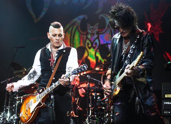 Актёр Джонни Депп (слева) и гитарист американской группы Aerosmith Джо Перри во время выступления на сцене спортивного комплекса Олимпийский