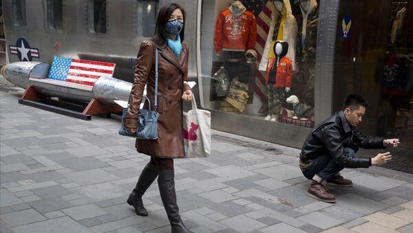 Прохожие возле магазина американских товаров в Пекине, КНР. Архивное фото