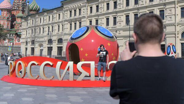 Молодые люди фотографируются рядом с символикой, посвященной предстоящему чемпионату мира по футболу 2018 в Москве. Архивное фото