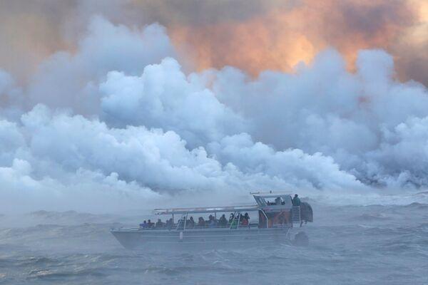 Пассажиры прогулочного катера наблюдают извержение вулкана Килауэа на Гавайях