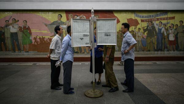 Жители Пхеньяна читают свежие выпуски газет, посвященные встречи лидеров КНДР и США. 12 июня 2018