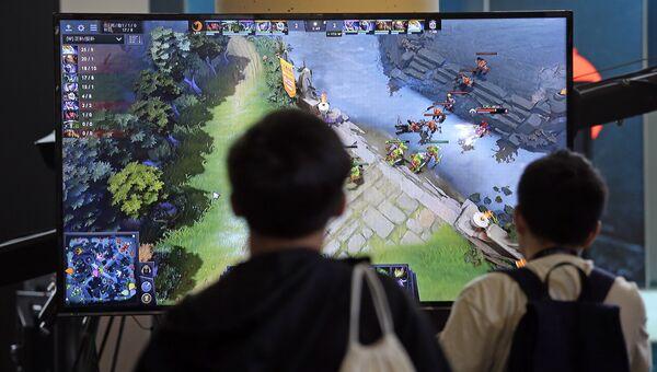 Подростки следят за игрой команд в Dota 2