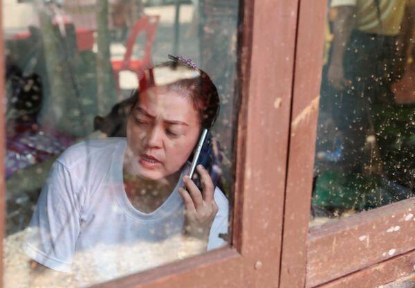 Родственница разговаривает по телефону неподалеку от пещерного комплекса, где были найдены дети