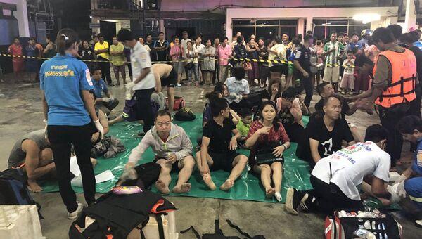 Сотрудники экстренных служб Таиланда оказывают помощь спасенным пассажирам перевернувшихся в районе Пхукета туристических лодок. 5 июля 2018