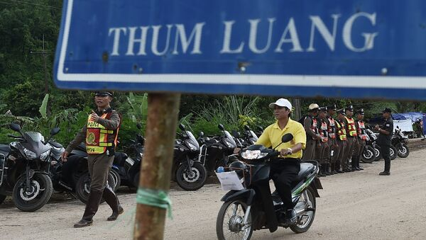 Тайские полицейские охраняют дорогу, ведущую к пещерной зоне Тхам Луанг, пока спасательная операция по вызволению детей продолжается. 9 июля 2018