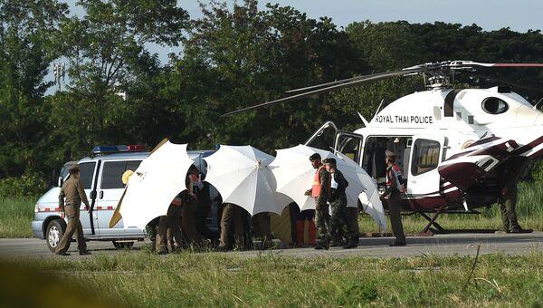 Спасенного из пещеры Тхам Луанг школьника эвакуируют с вертолета Королевской тайской полиции в ожидающую машину скорой помощи в военном аэропорту в Чианграе, Таиланд. 9 июля 2018