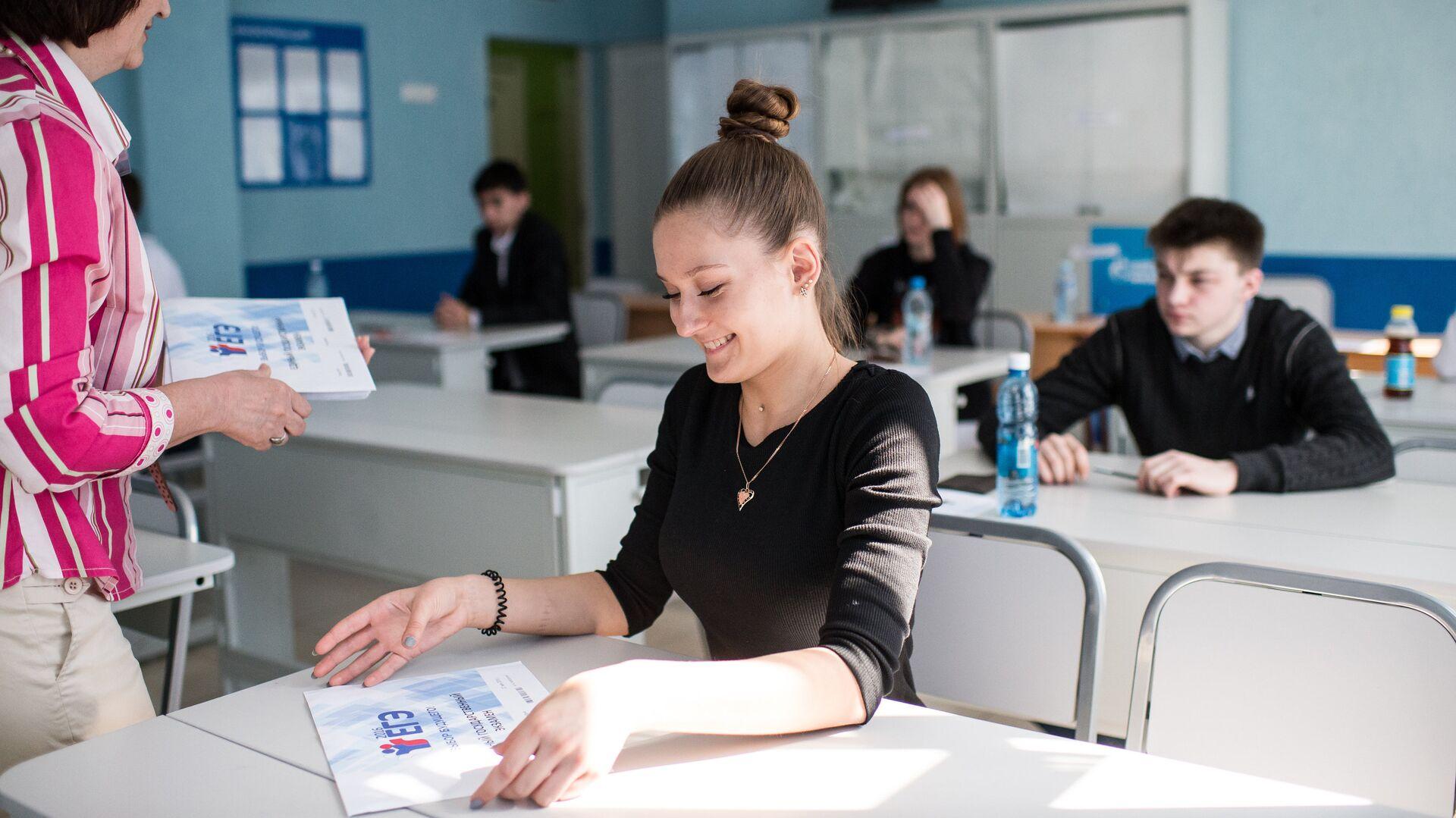 Преподаватель раздает пакеты с экзаменационными заданиями перед началом единого государственного экзамена по географии - РИА Новости, 1920, 10.06.2021